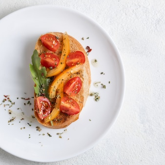 Bruschetta italiana con tomates en un plato blanco sobre fondo blanco. vista desde arriba
