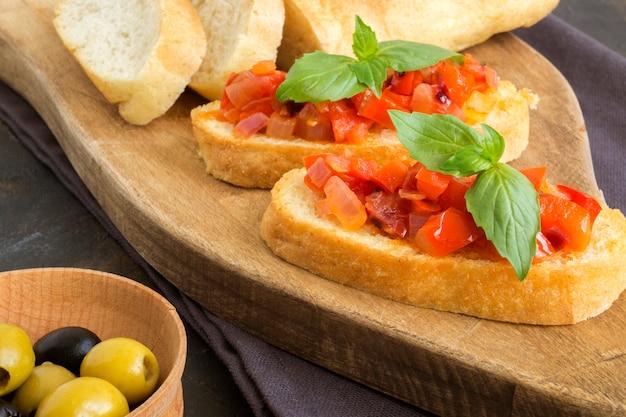 Bruschetta italiana tradicional con tomate, pimiento y albahaca