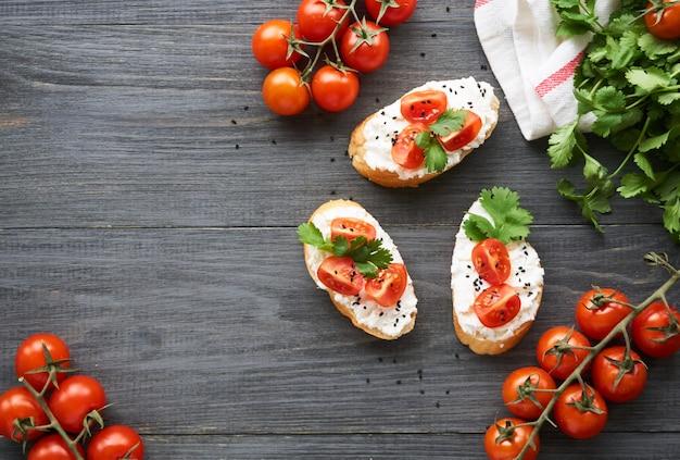 Bruschetta con queso ricotta, tomates cherry y cilantro sobre madera
