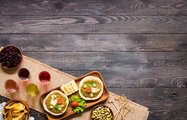 Bruschetta sabrosa y deliciosa con aguacate, tomate, queso, hierbas, papas fritas y licor, sobre un fondo de madera.