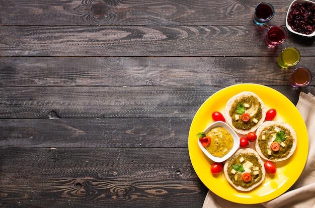 Bruschetta sabrosa y deliciosa con aguacate, tomate, queso, hierbas, papas fritas y licor sobre madera
