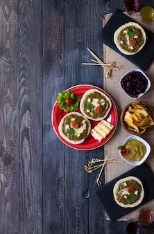 Bruschetta sabrosa y deliciosa con aguacate, tomate, queso, hierbas, papas fritas y licor.