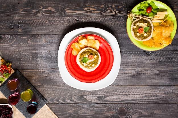 Bruschetta sabroso y delicioso con chips de hierbas de queso de aguacate tomates y licor sobre un fondo de madera.