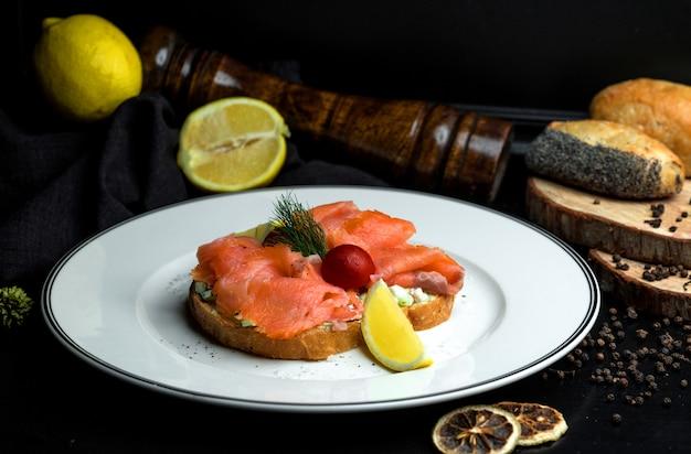 Bruschetta de salmón ahumado con aguacate servido con limón