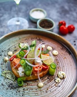Bruschetta de salmón con mozzarella de pepino eneldo cebolla roja tomate seco y lima