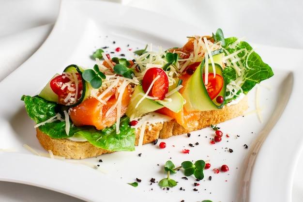 Bruschetta con salmón rojo pescado, verduras frescas y hierbas en un plato blanco