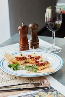 Bruschetta sobre una mesa de madera en un plato blanco y una copa de vino tinto