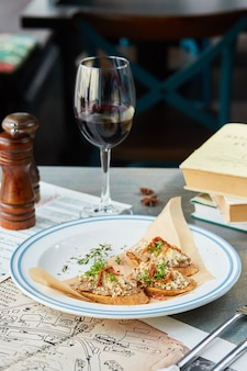 Bruschetta sobre una mesa de madera en un plato blanco y una copa de vino