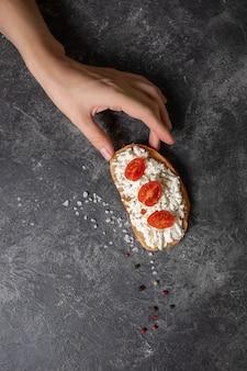Bruschetta con tomate y queso en las manos sobre un fondo oscuro, vista superior.