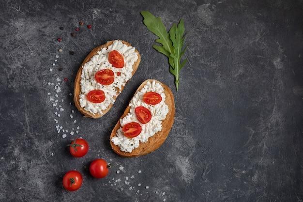 Bruschetta con tomate y queso sobre un fondo oscuro con verdes. vista superior, copia espacio.