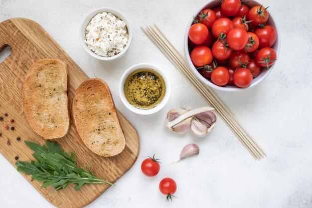 Bruschetta con tomates asados y queso mozzarella en una tabla de cortar
