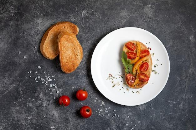 Bruschetta con tomates en un plato blanco sobre fondo oscuro, vista superior