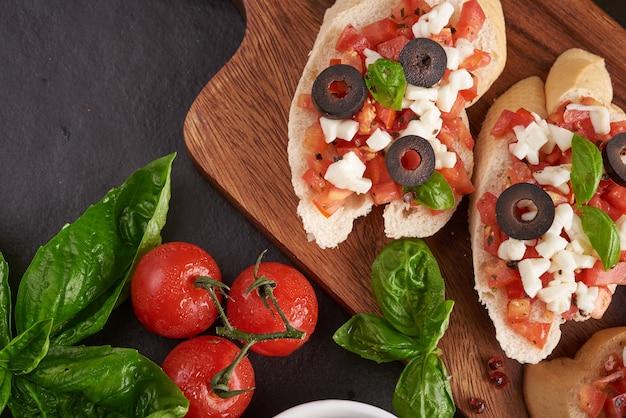 Bruschetta con tomates, queso mozzarella y albahaca sobre una tabla de cortar. aperitivo o refrigerio italiano tradicional, antipasto. bruschetta de ensalada caprese. vista superior con espacio de copia. endecha plana.