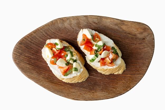 Bruschettas surtidas sobre una plancha de madera. areret snack. vista superior. aislado en blanco