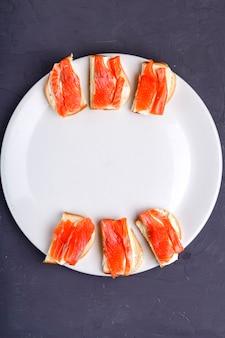 Bruschettes con caviar y mantequilla de trucha sobre una placa blanca sobre una superficie gris