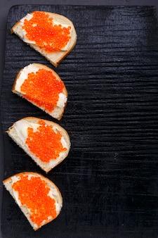 Bruschettes con mantequilla y caviar rojo dispuestos sobre una pizarra negra sobre una superficie de hormigón gris