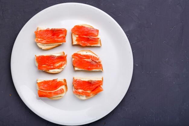 Bruschettes con mantequilla y salmón en una placa blanca sobre una superficie de hormigón gris