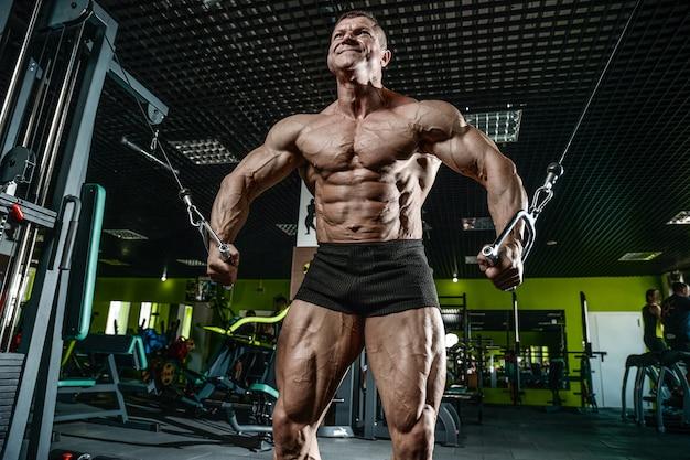 Brutal caucásico culturista entrenamiento cofre en gimnasio
