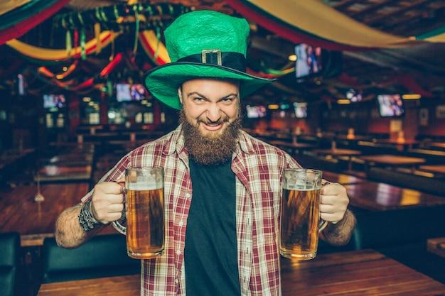 Brutal joven barbudo con sombrero verde de pie solo en pub. sostiene dos jarras de cerveza y mira. guy encogerse. el se ve feliz.