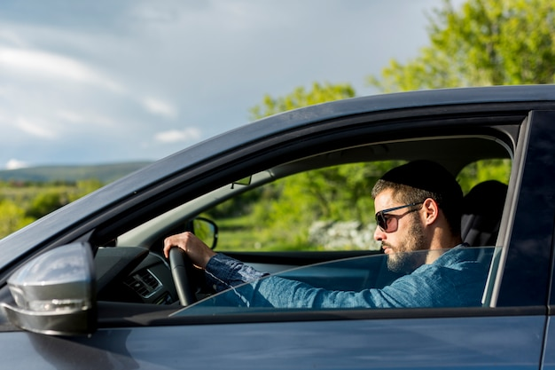 Brutal masculino con gafas de sol conduciendo coche