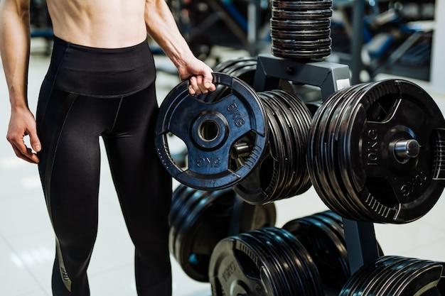 Brutal mujer atlética bombeando musculatura con pesas