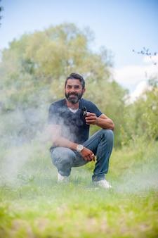 Brutalsmoker disfrutando de un dispositivo de humo electrónico sobre la hierba del bosque