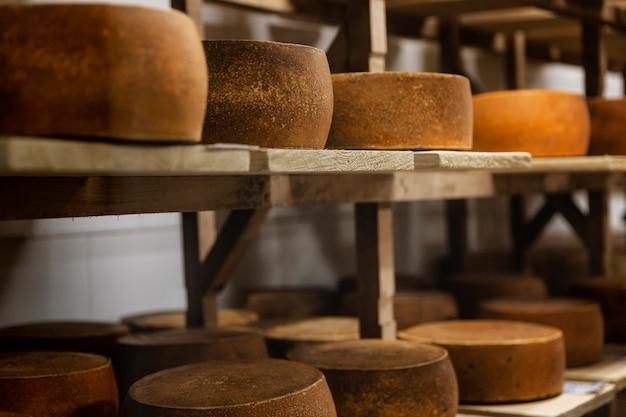 Bucles de queso en estantes de madera en un almacenamiento.