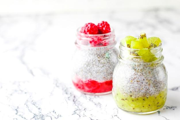 Budín con bayas, salsa de frambuesa, salsa de kiwi, frambuesas y moras congeladas y rodajas de kiwi