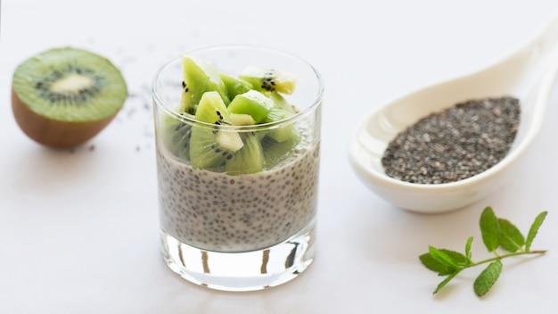 Budín de chía vegana saludable en un vaso con kiwi fresco