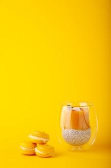 Budín de mango con semillas de chía en vidrio sobre fondo amarillo