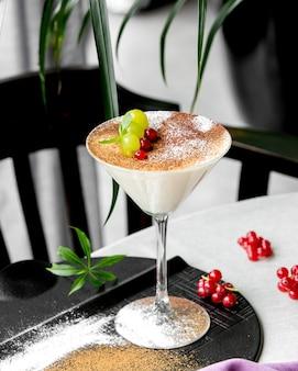 Budín de vainilla servido en copa de martini adornado con grosellas rojas y uvas