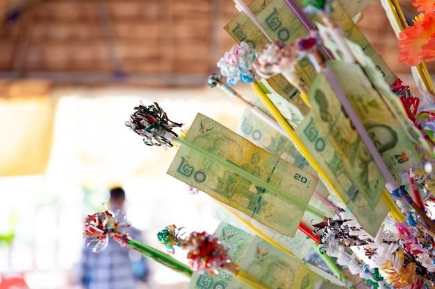 Los budistas tailandeses hacen un mérito con el billete de banco en el festival songkran. el festival songkran es la celebración tradicional del año nuevo en tailandia.