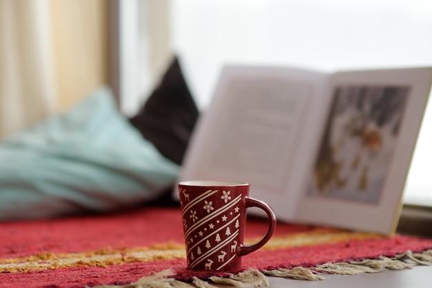 Un buen café y un buen libro. acogedora escena de invierno en casa.