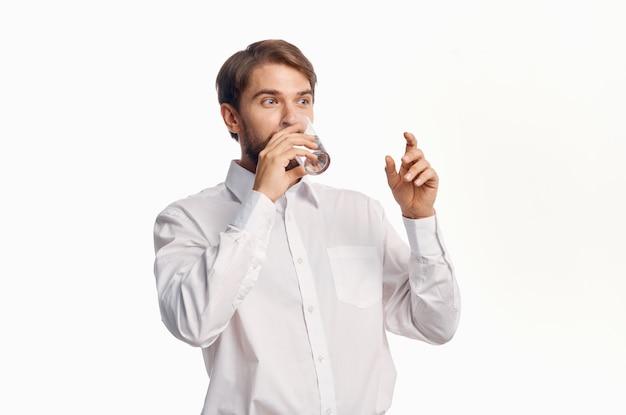 Buen chico bebiendo agua de un vaso y gesticulando con las manos.
