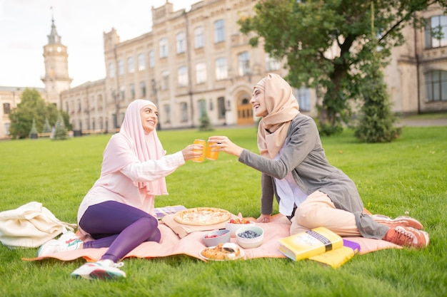 Buen descanso para almorzar. hermosos estudiantes musulmanes alegres con un agradable almuerzo fuera cerca de la universidad