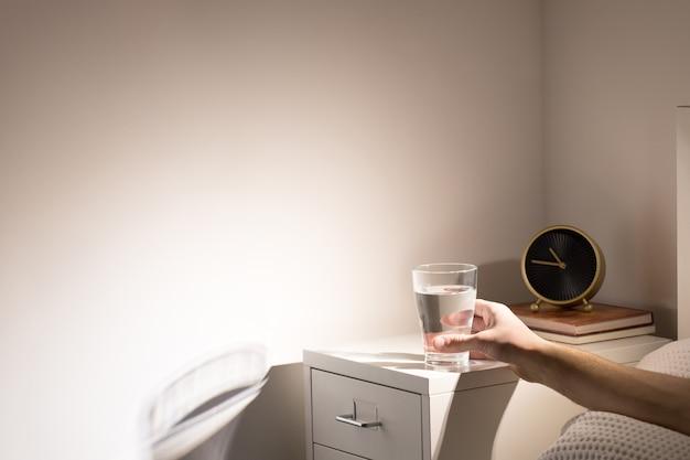 Buen hábito: beber un vaso de agua antes de irse a dormir. hombre en la cama tomando un vaso de agua de la mesita de noche antes de acostarse, copie el espacio.