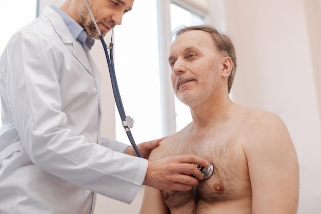 Buen hombre de pelo gris jubilado sentado en el consultorio del médico y haciendo lo que dice mientras espera su diagnóstico