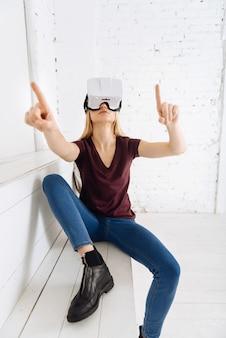 Buen humor. atractiva chica rubia levantando los dedos índice y agitando los brazos mientras está en máscara para visión virtual