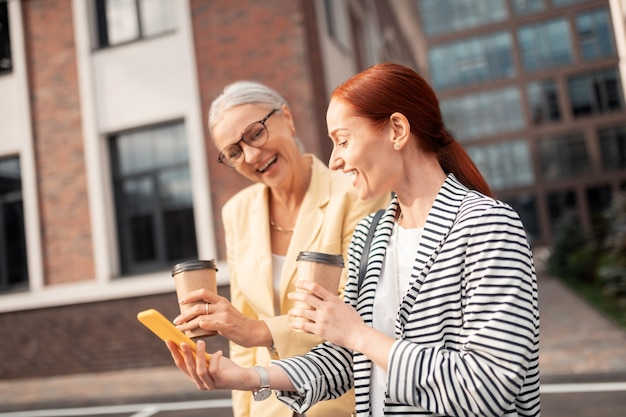 Buen humor. cintura para arriba de dos amigos contentos con ropa elegante riendo al aire libre frente a un edificio de oficinas