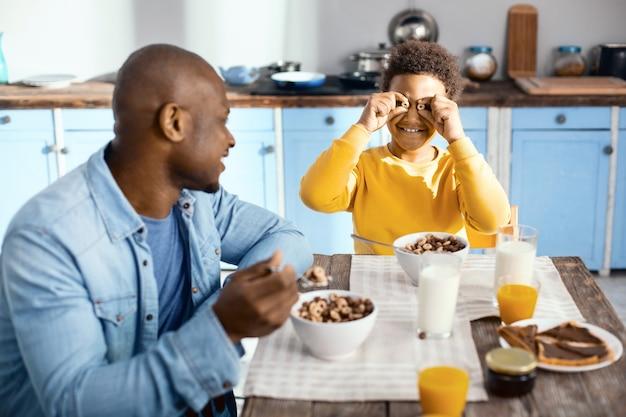 Buen humor. encantador bot preadolescente sentado a la mesa y sosteniendo dos anillos de cereal cerca de sus ojos, bromeando con su padre mientras desayuna