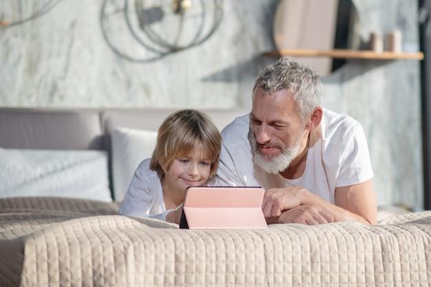 Buen humor. feliz papá sonriente con el bebé acostado en la cama sobre el estómago apoyado en los codos mirando tablet