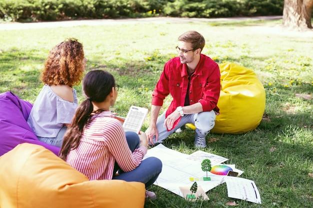 Buen humor. guapo hombre decidido hablando con sus compañeros de trabajo mientras trabaja al aire libre