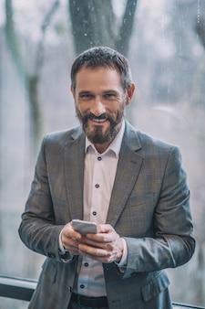 Buen humor. hombre barbudo adulto alegre en traje gris de negocios con smartphone de pie de espaldas a la ventana en la oficina