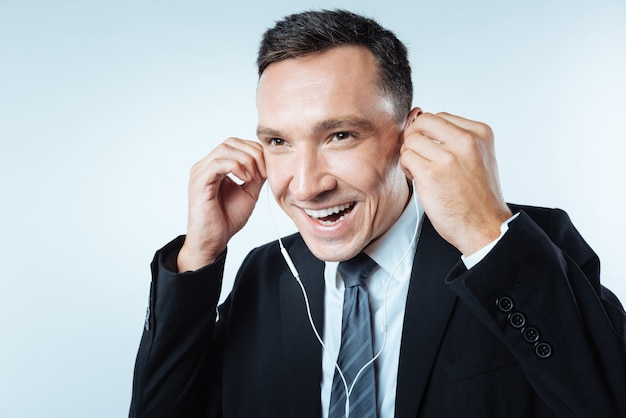 Buen humor. hombre guapo alegre feliz sosteniendo auriculares y poniéndolos en sus oídos mientras está de buen humor