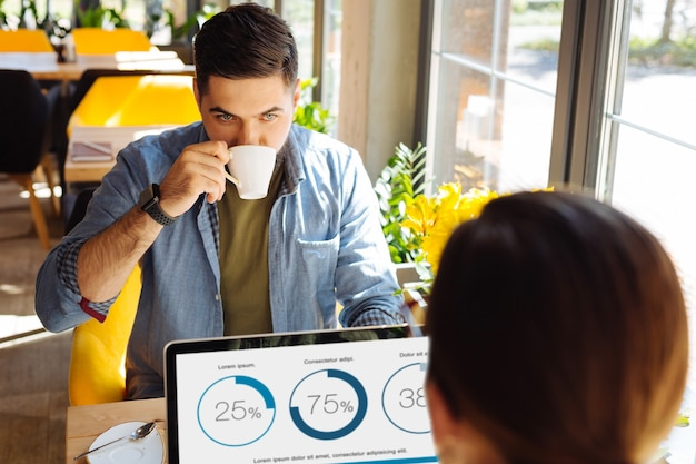 Buen humor. hombre guapo feliz mirando la taza de café mientras está sentado frente a su colega