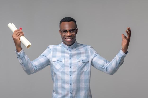 Buen humor. hombre sonriente adulto joven de piel oscura con gafas con papeles en la mano y gesto abierto