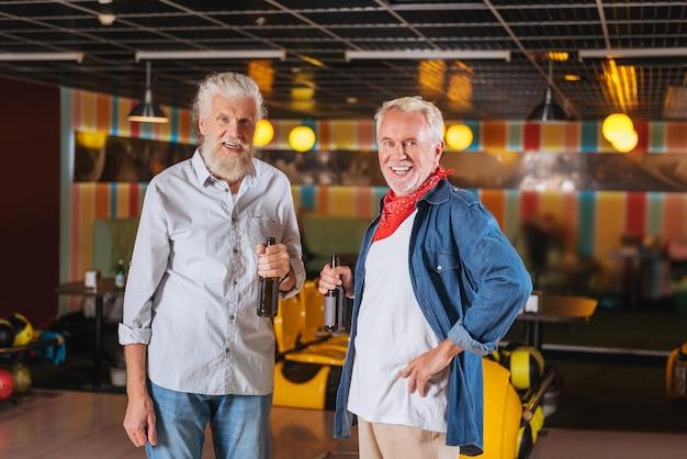Buen humor. hombres alegres positivos de pie bebiendo cerveza mientras se divierten en la bolera