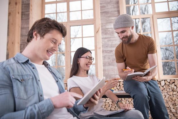 Buen humor. jóvenes alegres positivos sentados juntos y sonriendo mientras disfrutan de su conversación