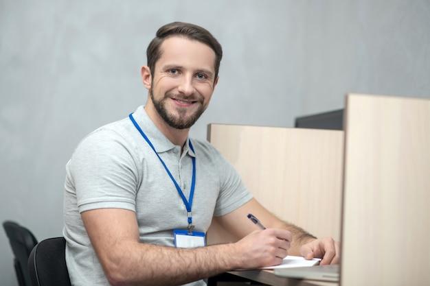 Buen humor. sonriente joven adulto con placa sentado en la oficina trabajando de buen humor