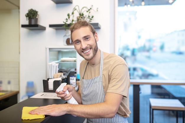 Buen humor. sonriente joven atractivo barbudo con desinfectante y servilleta de pie cerca del mostrador en la superficie de limpieza de café